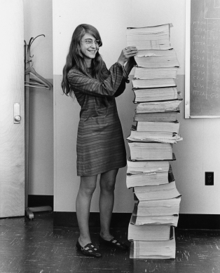 Margaret Hamilton next to the pages of code